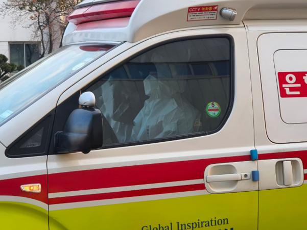 31일 오전 8시 30분쯤 서울 강서구 김포공항 비즈니스항공센터(SGBAC)를 빠져나가는 구급차량의 모습. 앞좌석에 탄 구급대원들이 마스크와 흰색 방호복을 착용하고 있다. /정민하 기자