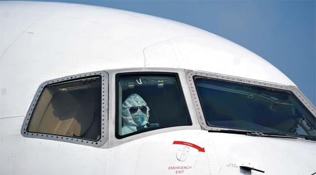 신종 코로나 바이러스 감염증(우한 폐렴)이 발생한 중국 우한시 공항에서 지난달 28일 한 화물기 조종사가 방진복과 마스크를 착용하고 조종석에 앉아 있다. 우한 폐렴 감염 공포 확산으로 항공사들이 중국 노선을 잇따라 폐쇄하면서, 4일 기준 국내 항공사들의 중국 노선 운항률(향후 운항 중단 일정 반영)은 31%대까지 떨어졌다.