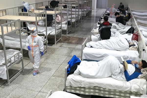 5일 중국 후베이성 우한의 한 대형 전시장을 개조한 임시병원에서 보호복을 입은 의료진이 신종 코로나바이러스 감염증 환자들 옆을 지나가고 있다. /AP=연합뉴스