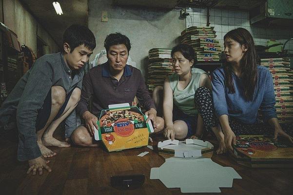 영화 '기생충'에서 브리아나 그레이가 올린 피자 박스 접기 영상을 보면서 아르바이트를 하는 기택의 가족.