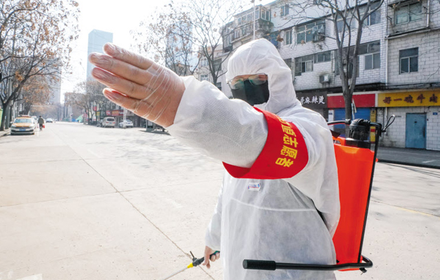신종 코로나 바이러스 감염증이 시작된 중국 우한시에서 지난 9일 방역복을 입은 한 자원봉사자가 거리를 소독하고 있는 모습. 중국 현지 기업들이 최근 업무를 재개하면서 중국 내 다른 도시에 진출해 있는 한국 기업 주재원들도 잇따라 복귀했지만, 식자재·마스크 등의 공급이 뚝 끊기는 등 환경이 열악하다.