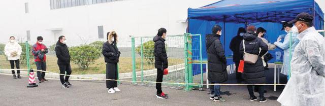 """13일 중국 장쑤성 우시시 소재 한국콜마 공장 직원들이 출근 전 마스크를 쓰고 줄지어 체온 측정을 기다리고 있다. 회사 관계자는 """"체온이 37.5도 이상인 직원은 곧바로 현지 정부에 보고된다""""고 했다."""