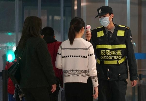 신종 코로나바이러스 진원지인 중국 후베이성 우한의 톈허 국제공항에서 지난달 21일 한 검역관이 우한을 떠나는 여행객들의 체온을 측정하고 있다. /연합뉴스