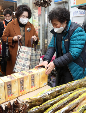 지난 18일 오후 김정숙(왼쪽) 여사가 서울 중랑구 면목동 동원전통종합시장의 건어물 상점에서 꿀을 사고 있다.