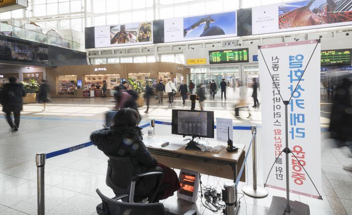 20일 오전 서울 중구 서울역 역사 2층 출입구 앞에서 중구보건소 관계자가 열감지 카메라를 통해 지나가는 사람들의 체온을 확인하고 있다.