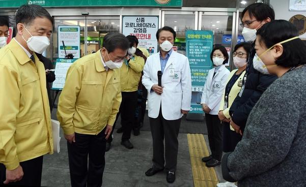 문재인 대통령이 25일 대구의료원에서 파견의료진(오른쪽 사복입은 두명) 등에게 인사하고 있다. /연합뉴스