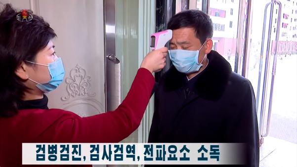 북한 조선중앙TV는 신종 코로나바이러스 감염증(코로나19) 예방 조치로 주민들에 대한 검병검진을 철저하게 하고 있다고 지난 27일 보도했다. 사진은 중앙TV 방송화면으로, 마스크를 낀 주민이 체온측정을 받고 있다. /조선중앙TV 캡처