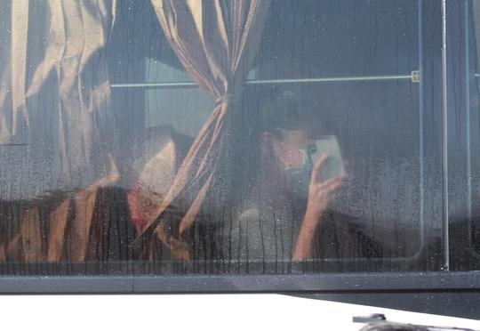 코로나19로 아산 임시생활시설에 격리됐던 한 우한교민이 지난달 15일 오전 충남 아산시 초사동 경찰인재개발원을 버스로 떠나며 스마트폰으로 촬영하고 있다. /연합뉴스