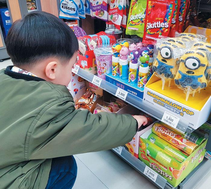 23일 서울 성동구에 있는 편의점 이마트24 성수삼환점에서 한 어린이가 어린이용 상품을 고르고 있다.