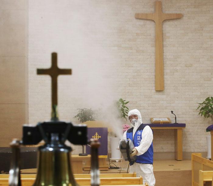 23일 오후 서울 마포구의 한 교회에서 방역복을 입은 구청 직원이 분사기로 소독약을 살포하고 있다.
