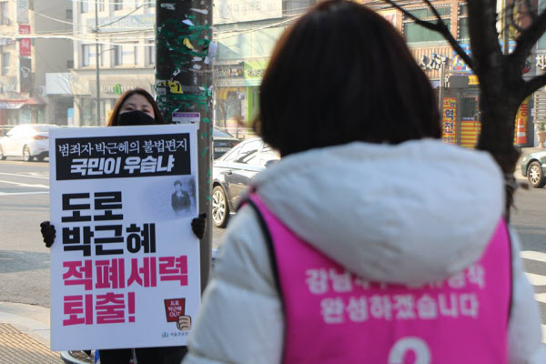 나경원 통합당 의원이 유세를 위해 나서자, 친여성향 지지자로 보이는 한 여성이 '범죄자 박근혜' 피켓을 들어보이고 있다./나경원 페이스북