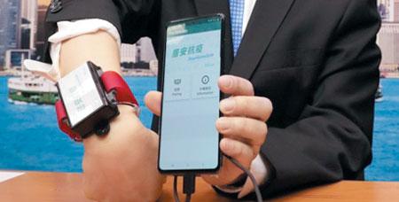 홍콩 정부의 정보통신 책임자가 방송에 출연해 외국 입국자의 동선을 추적할 수 있는 GPS 전자팔찌를 보여주고 있다.