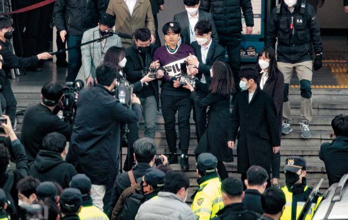 """모습 드러낸 '박사' 취재 열기 - 여성들을 협박해 성(性) 착취 불법 촬영물을 제작하고 유포한 텔레그램 '박사방' 운영자 조주빈(25)이 25일 오전 서울 종로경찰서를 나서며 취재진의 질문을 받고 있다. 이날 종로경찰서 정문 밖에서는 100여명이 모여 """"법정최고형을 구형하라"""" """"공범자도 처벌하라"""" 등의 문구가 쓰인 피켓을 들고 항의 시위를 벌였다."""