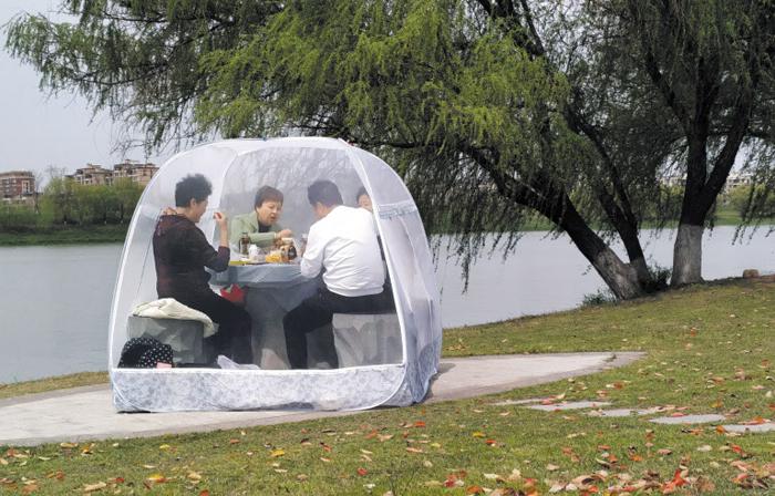 이렇게 텐트 치고 먹으면 코로나 예방? - 중국 장쑤성 난징(南京)의 한 공원에 설치된 탁자 위에 24일 시민들이 텐트를 쳐 놓고 밥을 먹고 있다. 외신들은 코로나 바이러스를 예방하기 위한 차원이라고 설명했다. 중국에서는 코로나 감염자 수가 현격히 줄어들고 있지만, 통계에 잡히지 않는 무증상 감염자의 수가 여전히 많아 재확산 우려가 사그라들지 않고 있다.