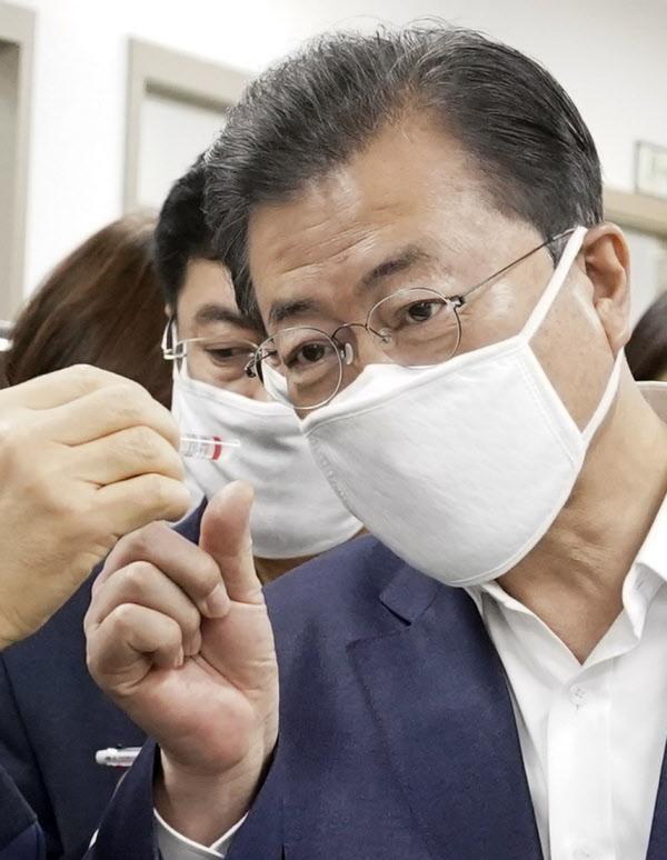 문재인 대통령이 25일 코로나19 진단시약 긴급사용 승인 기업 중 하나인 송파구 씨젠에서 시약 제품을 보고 있다. /연합뉴스