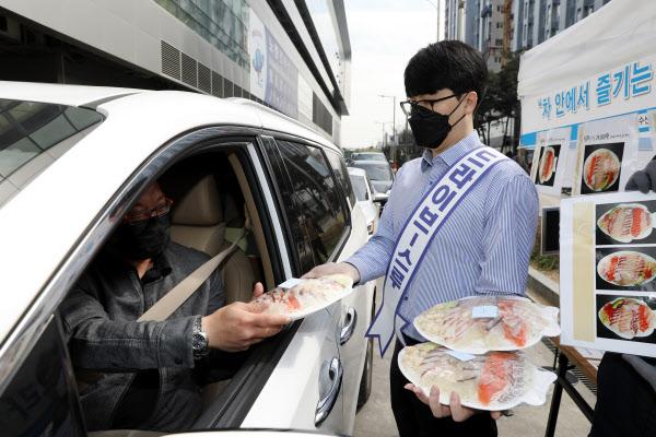 2. 서울 동작구 노량진수산시장에 설치된 드라이브 스루 판매 부스에서 직원이 차 안의 고객에게 모둠회를 건네고 있다./수협중앙회 제공