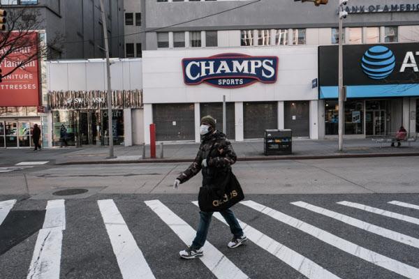 미국 뉴욕에서 한 시민이 26일(현지 시각) 문이 닫힌 상점들 앞의 한산한 거리를 걸어가고 있다./로이터 연합뉴스