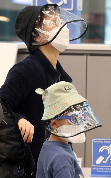 미국에서 27일 인천국제공항을 통해 귀국한 시민들이 비닐창이 있는 모자를 착용하는 등 완전무장을 하고 있다./연합뉴스