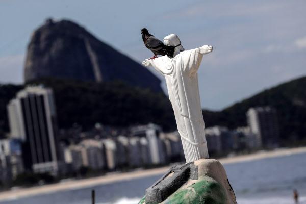 브라질 리우데자네이루 시의 예수상 모형에 지난달 31일 검은색 마스크가 붙어 있다./연합 EPA