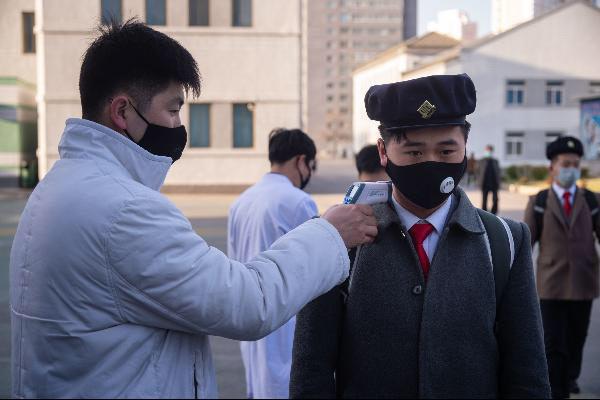 북한 대학생이 지난달 평양의 한 대학에서 마스크를 쓰고 발열 검사를 받고 있다. /AFP 연합뉴스
