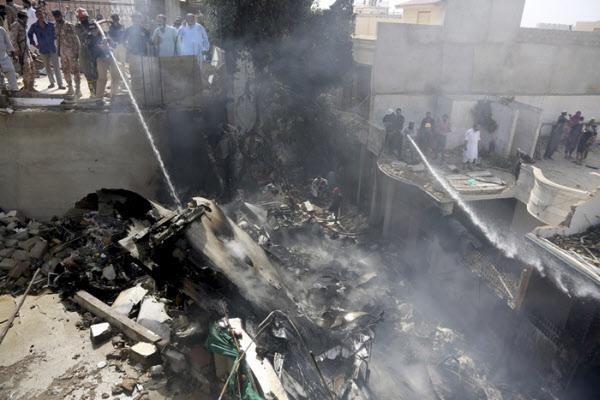 22일 파키스탄 카라치의 주택가에서 구조대원들이 여객기 추락 사고로 인한 화재를 진압하고 있다./AP 연합뉴스