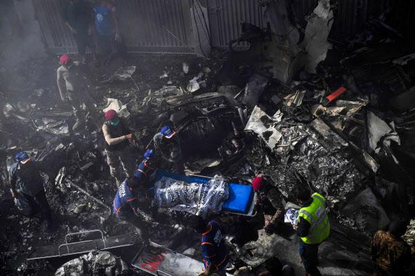 22일 파키스탄 카라치의 주택가에서 구조대원들이 여객기 추락 사고로 인한 화재를 진압하고 있다./AFP 연합뉴스