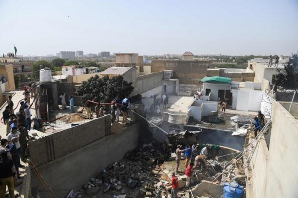 22일 파키스탄국제항공 여객기가 추락한 현장에서 구조대원들이 시신을 옮기고 있다./AFP 연합뉴스