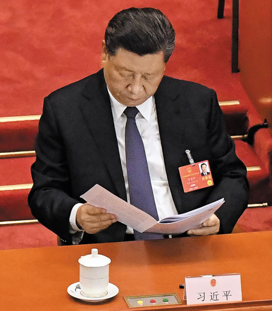 22일 중국 베이징에서 열린 전국인민대표대회에서 시진핑 중국 국가주석이 리커창 총리가 연설하는 동안 관련 서류를 보고 있다.