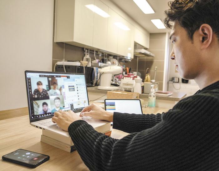 SK텔레콤의 한 직원이 자신의 집에서 컴퓨터로 팀원들과 화상회의를 하며 근무하고 있다.