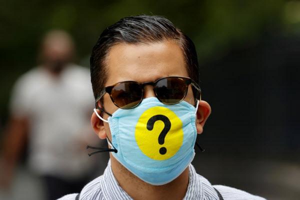 22일(현지시각) 뉴욕 맨하탄에서 '물음표'가 들어간 마스크를 쓴 시민의 모습 /로이터 연합뉴스