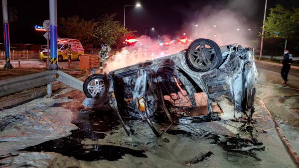 지난 23일 밤 10시14분쯤 부산 강서구 대저동 서부산유통단지 입구에서 20대 여성이 몰던 쏘울 승용차가 도로 중앙 가드레일을 들이받고 뒤집힌 뒤 불이 나 타고 있다. 차 안에 타고 있던 운전자는 사고를 목격한 50대 남성이 구조해 큰 피해는 입지 않았다. /부산경찰청 제공