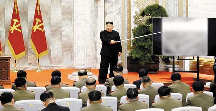 김정은 북한 국무위원장이 긴 막대로 스크린을 가리키며 노동당 중앙군사위원들에게 무언가를 설명하고 있다.