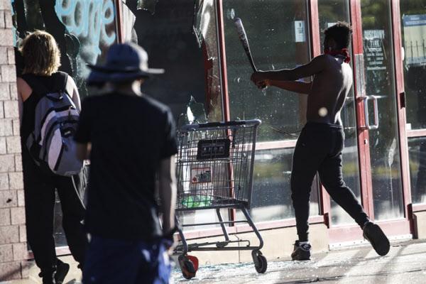 미네소타 세인트 폴에서 한 흑인이 상점의 유리창을 야구방망이로 깨고 있다/AP 연합뉴스