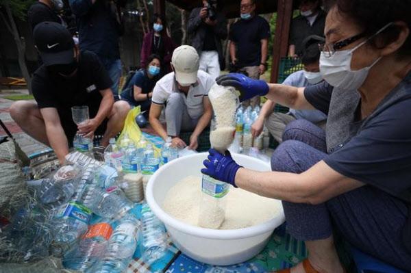 탈북민 단체 '큰샘' 회원들이 지난 18일 오전 서울 북한에 보낼 쌀을 페트병에 담고 있다. 이들은 21일 강화 석모도에서 페트병에 쌀과 마스크를 담아 북한에 보내려했으나, 주민들의 반발로 무산됐다. /뉴시스