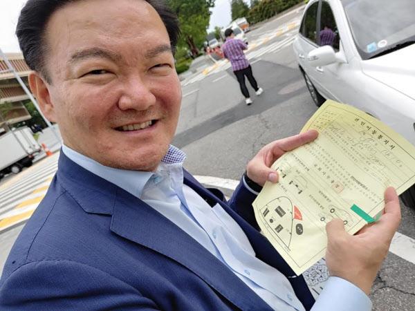 민경욱 전 미래통합당 의원이 견인 통지서를 받아들고 웃고 있는 모습. /차명진 전 미래통합당 의원 페이스북