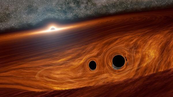 초거대 블랙홀의 강착원반번에서 아래쪽 블랙홀 두 개가 충돌하는 모습의 상상도. 블랙홀 충돌로 중력파가 발생하고 이로 인해 강착원반의 물질에서 빛의 폭발이 일어나는 현상이 관측됐다./칼텍