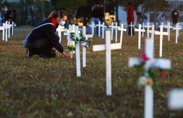 28일(현지 시각) 중남미에서 코로나 상황이 가장 심각한 브라질의 수도 브라질리아에서 한 반정부 시위자가 코로나 감염증으로 사망한 이들을 기리기 위한 십자가에 꽃을 놓고 있다. /AFP 연합뉴스