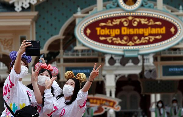 1일 재개장한 도쿄 디즈니랜드에서 관광객들이 마스크를 쓴 채 기념사진을 찍고 있다. /로이터 연합뉴스