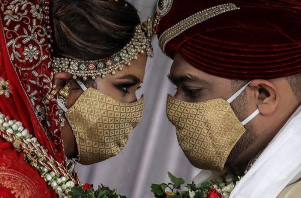 지난달 인도 뭄바이에서 열린 결혼식에서 신랑과 신부가 마스크를 쓴 채 마주보고 있다. 기사 내용과 관련 없음./EPA 연합뉴스