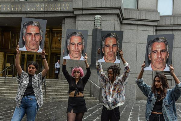 작년 7월(현지 시각) '핫 메스'라는 단체가 미국 뉴욕시 연방법원 앞에서 제프리 엡스타인의 얼굴이 그려진 간판을 들고 서 있다. '억만장자' 제프리 엡스타인의 전 여자친구 기슬레인 맥스웰이 목요일 미국 연방수사국(FBI)에 체포됐다./AFP 연합뉴스