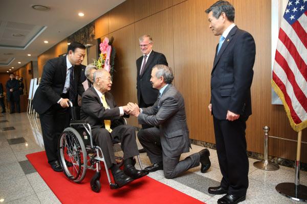 2018년 11월 21일 서울 용산구 국방컨벤션에서 주한미군이 주관한 백선엽 예비역(왼쪽 둘째) 대장 생일파티에서 해리 해리스(오른쪽) 주한 미 대사가 무릎을 꿇고 맞이하고 있다./조선일보DB