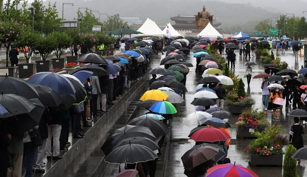 13일 서울 광화문 광장에 마련된 백선엽 장군 추모 분향소에 추모를 위해 방문한 시민들이 우산을 쓰고 줄을 서 있다./조선DB