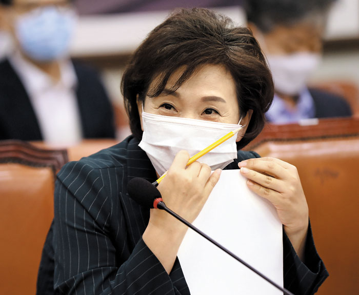 김현미 국토교통부 장관이 29일 오전 국회 국토교통위원회 전체회의에 참석해 마스크를 쓴 채 웃고 있다.