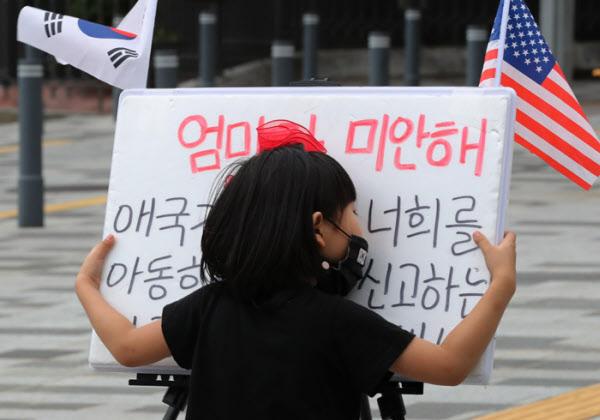 아직도 엄마의 손이 많이 필요한 6살짜리 딸 이정아양이 '엄마가 미안해..'라고 쓰여진 팻말을 보듬고 있다.아이들은 애국가 맘에게 존재 이유중의 하나이다. /이진한기자