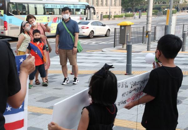 지난 18일 토요일 애국가 맘의 남매가 애국가를 부르는 모습을 역시 남매를 데리고 서울 시내에 나온 한 시민의 가족이 관심있게 보고있다./이진한기자