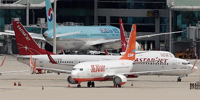 지난 7월 14일 오전 인천국제공항 여객터미널에 제주항공 비행기와 이스타항공 비행기가 멈춰 서 있다. photo 뉴시스