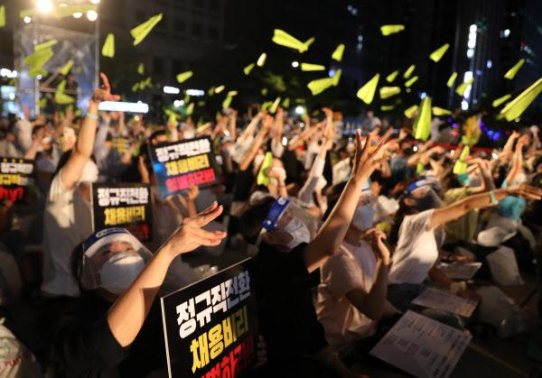 1일 서울 중구 청계천로 일대에서 열린 '투명하고 공정한 정규직 전환 촉구 문화제' 참가자들이 '공정한 과정'을 의미하는 연두색 종이 비행기를 하늘로 날려 보내고 있다. /뉴시스