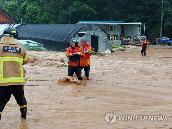 2일 집중호우가 내린 충북 단양의 한 마을 주민들이 불어난 빗물로 마을 진입로가 끊기자 119구조대의 도움을 받아 안전지대로 대피하고 있다. /연합뉴스