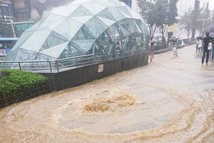 수도권 전역에 호우 특보가 내려진 1일, 서울 강남역 주변 맨홀 구멍에서 폭우로 늘어난 하수가 역류해 인도가 흙탕물로 뒤덮여 있다.