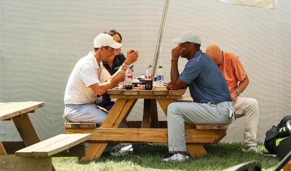 Tiger Woods (오른쪽)와 Rory McIlroy는 경기 후 클럽 하우스 옆 야외 피크닉 테이블에서 햄버거와 콜라를 마시고 있습니다 ./Getty Images